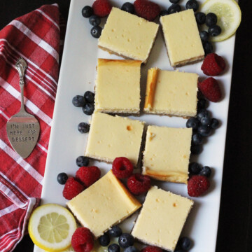 tray of cheesecake squares with fresh berries