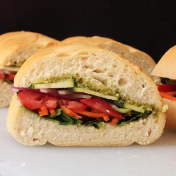 A close up of a Veggie Pesto sandwich on a cutting board