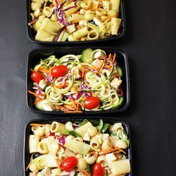 black meal prep containers with different pasta salads