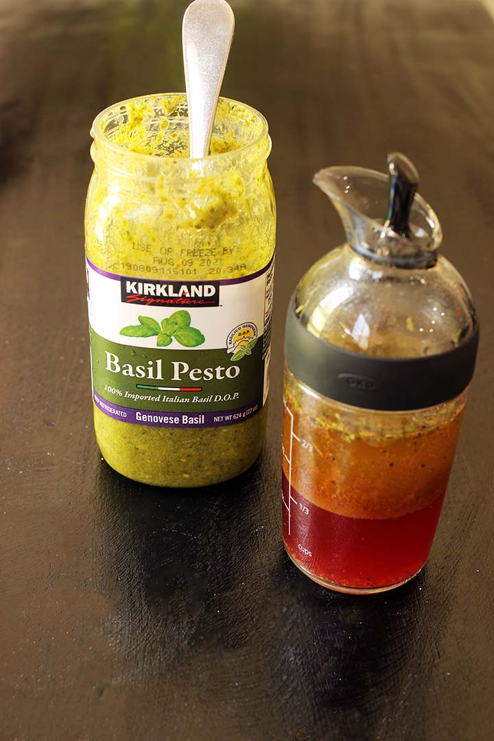 jar of pesto and salad dressing decantor on black table