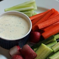A cup of ranch on plate of veggies