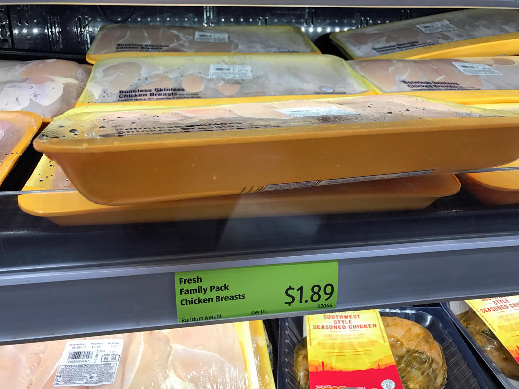 trays of chicken on shelf at store