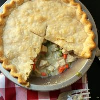 pot pie with slices removed next to fork and red checked cloth