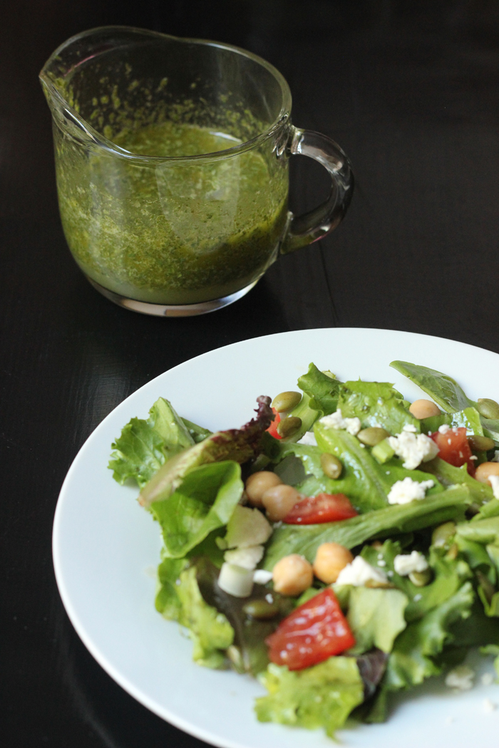 salad on a plate with cilantro lime dressing in a container