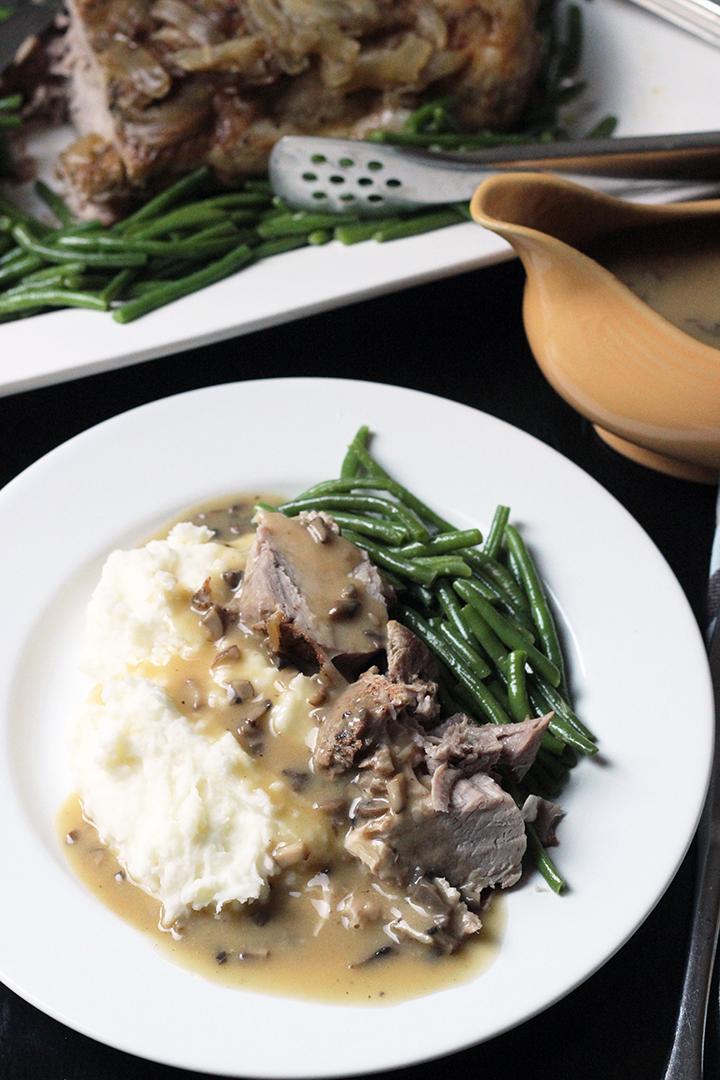 dinner plate of pork roast potatoes gravy and green beans