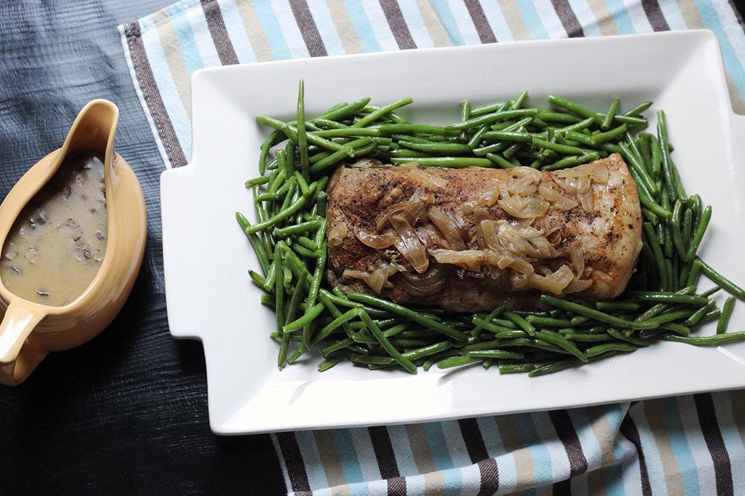 pork loin roast on platter with green beans next to gravy boat full of mushroom sauce