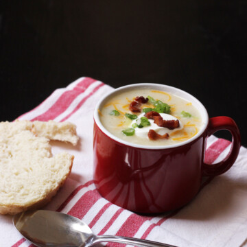A mug of Soup with roll and spoon