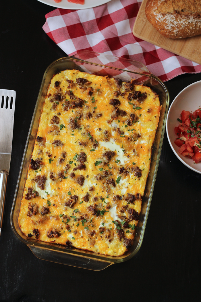 pan of sausage potato breakfast casserole on table with side dishes
