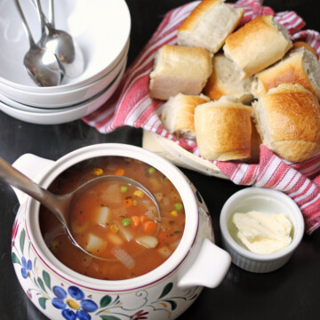 A tureen of soup on a table, with bread