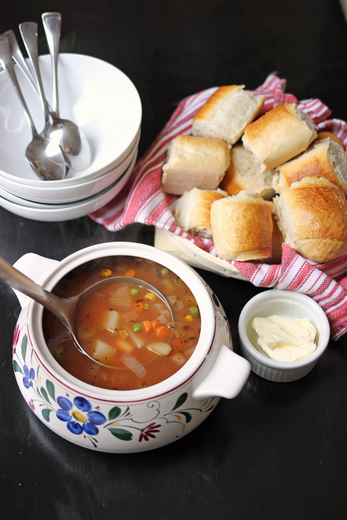 bowl of vegetable soup with a basket of rolls