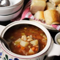 tureen of spicy vegetable soup with basket of rolls