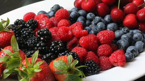 tray of berries with toppings on the side
