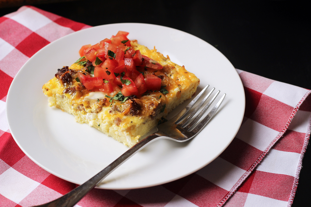 Slice of Sausage Egg Hash Brown Casserole on a plate with a fork