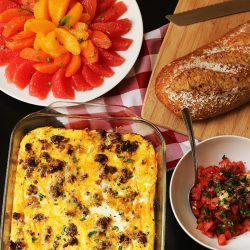 breakfast table with fruit egg cassserole bread and bruschetta