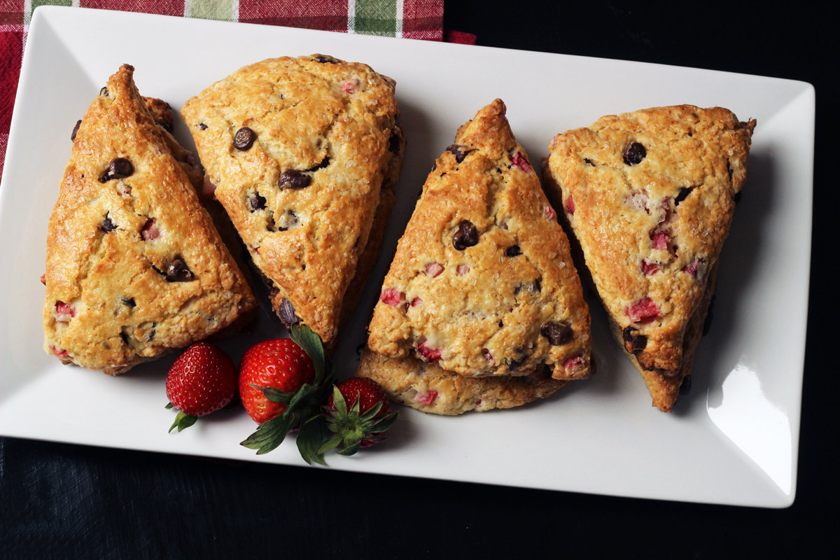 four stacks of chocolate strawberry scones on a white platter with strawberries