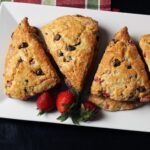 chocolate strawberry scones on platter with strawberries.