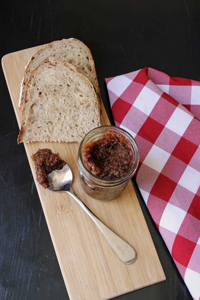 cutting board with english pickle, spoon and bread on it