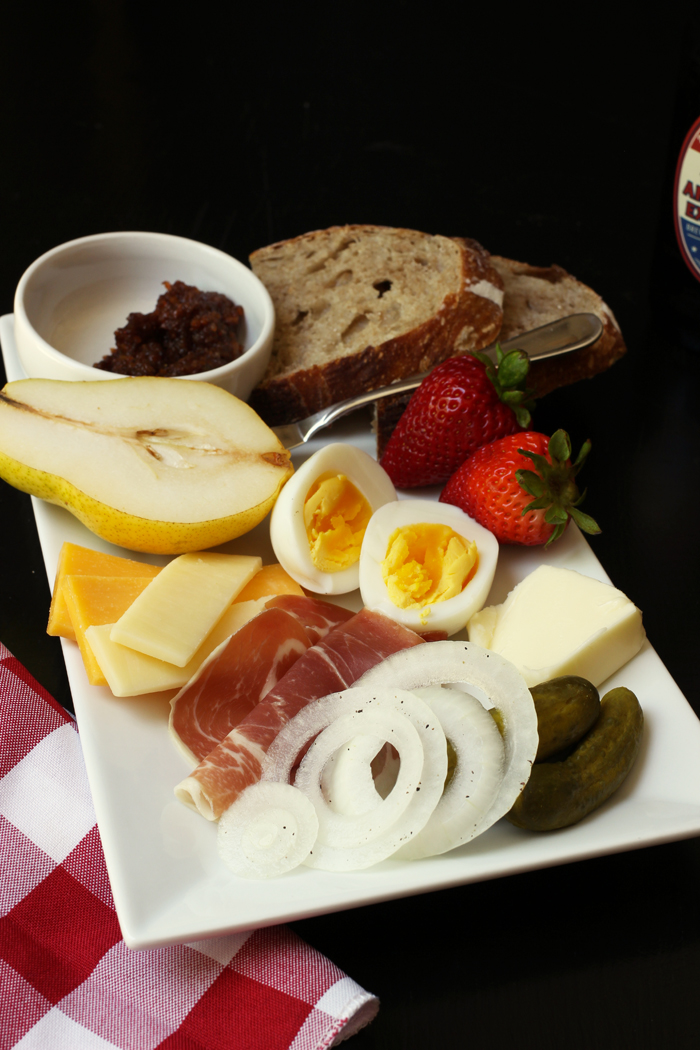ploughman's lunch with eggs, ham, bread, pickle, cheese, and fruit
