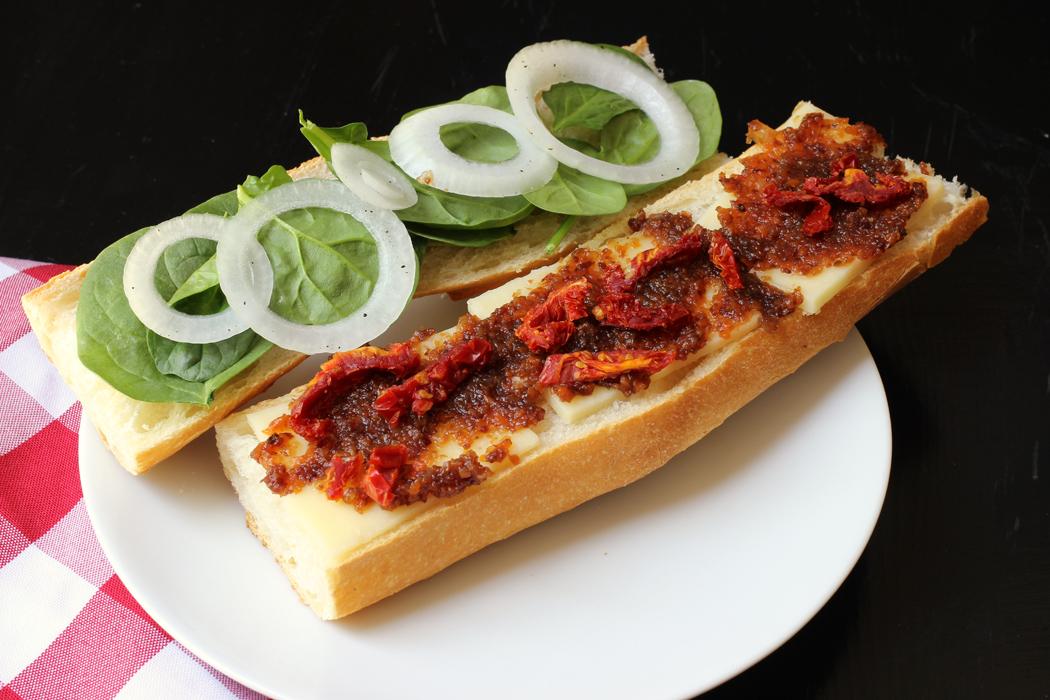assembling a posh cheddar and pickle baguette sandwich