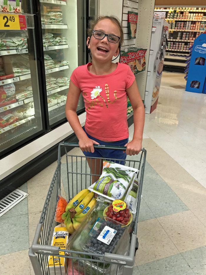 girl with little shopping cart in grocery store