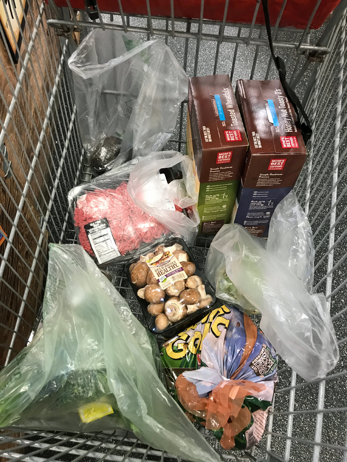meat, vegetables, and other groceries in cart