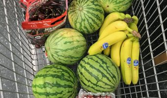 grocery cart full of watermelons, cherries, and bananas