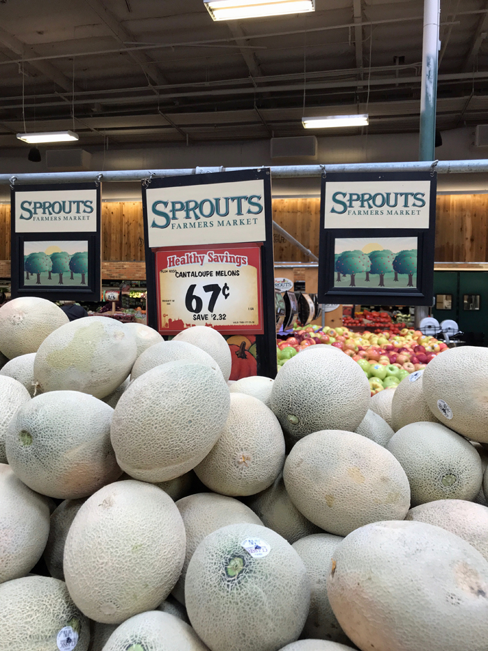 stack of melons on sale at a Sprouts grocery store