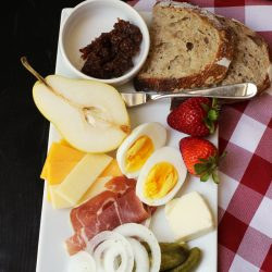 plate of meats, cheeses, egg, fruit, and pickle