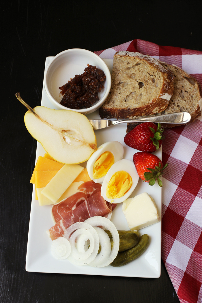 white platter with fruit, meat, cheese, bread, eggs, and pickles