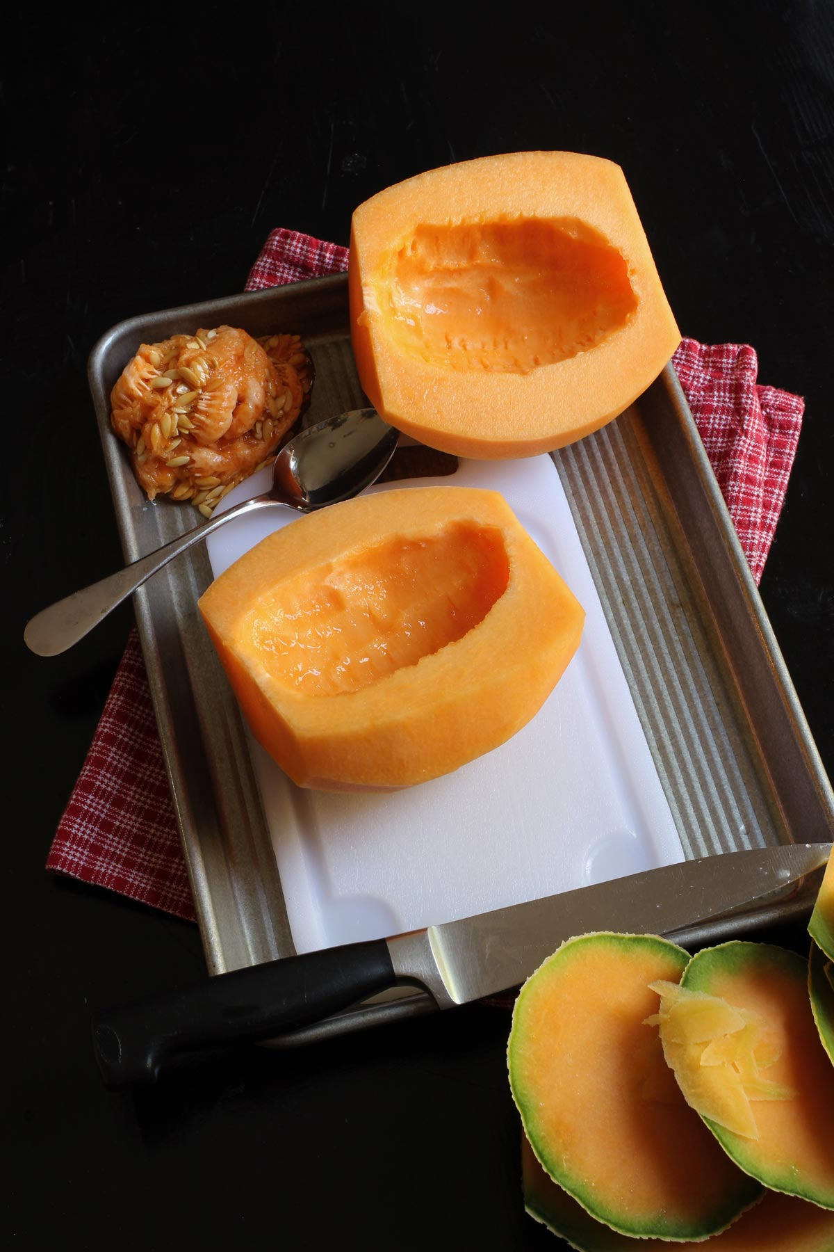 cantaloupe halves without seeds on cutting board with pile of seeds nearby.