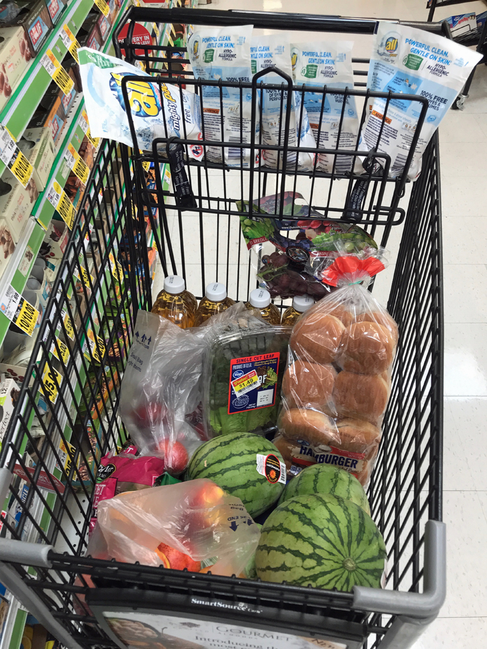 A grocery cart with watermelons and other foods