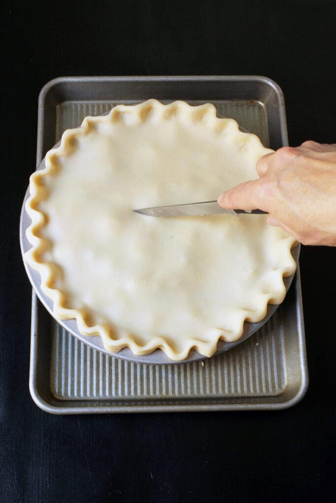 cutting vent holes in top crust of pie