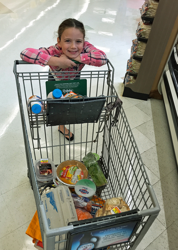 girl holding on Shopping Cart at store