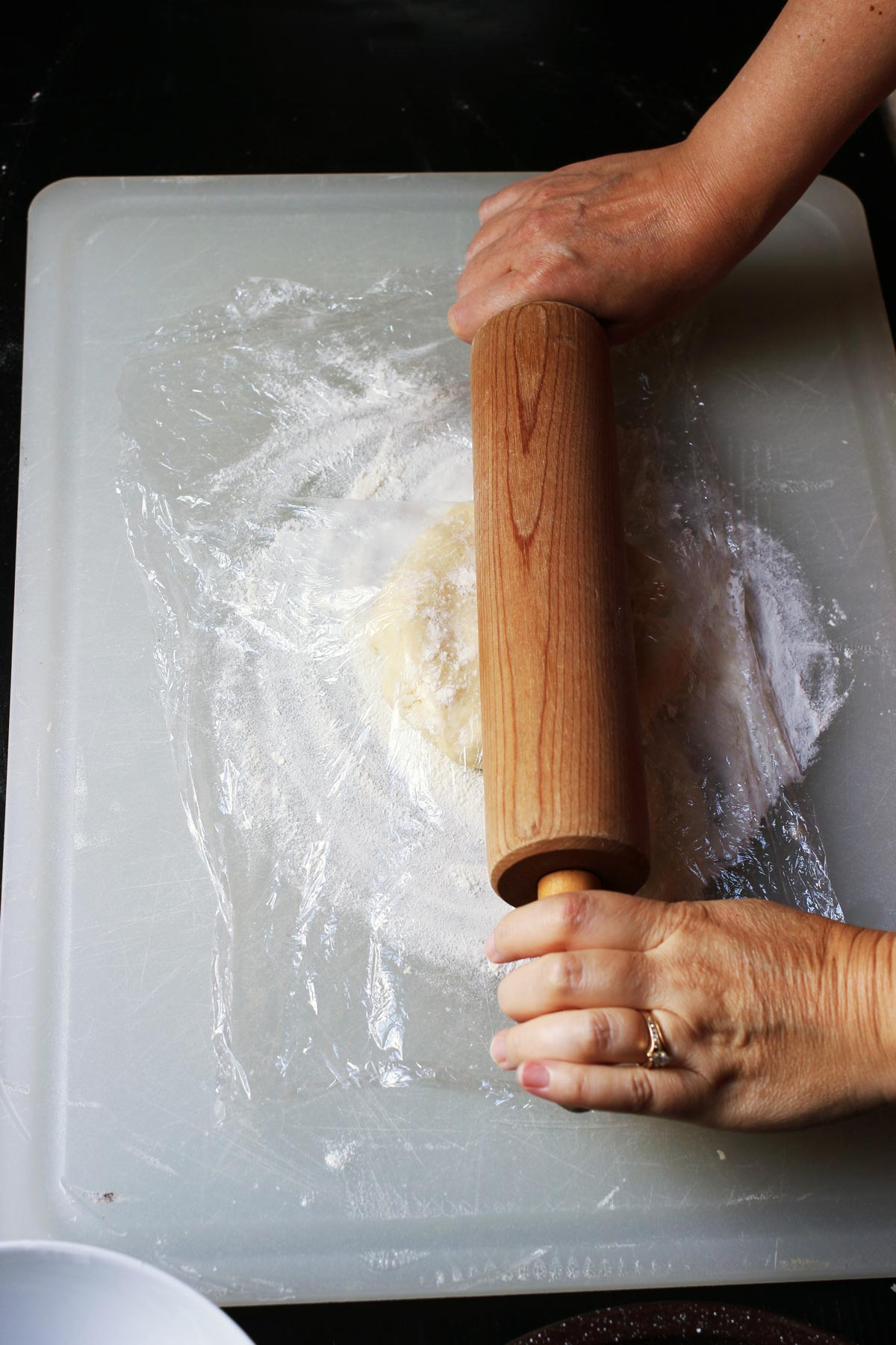 rolling pie dough with pin and plastic wrap