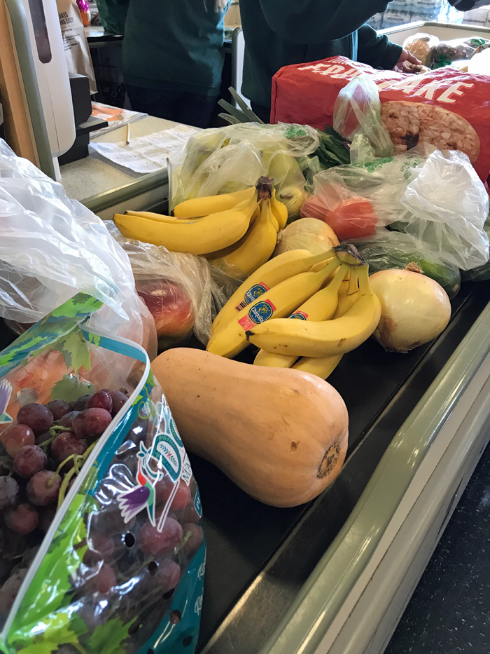 bananas and other groceries on conveyor belt