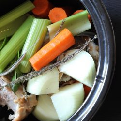 vegetables and turkey stock ingredients in slow cooker