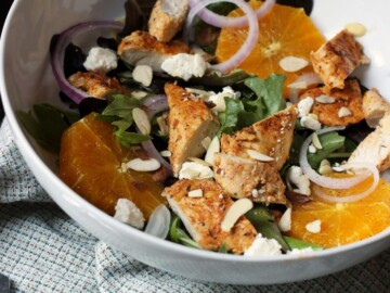 salad in white bowl with chicken and orange slices