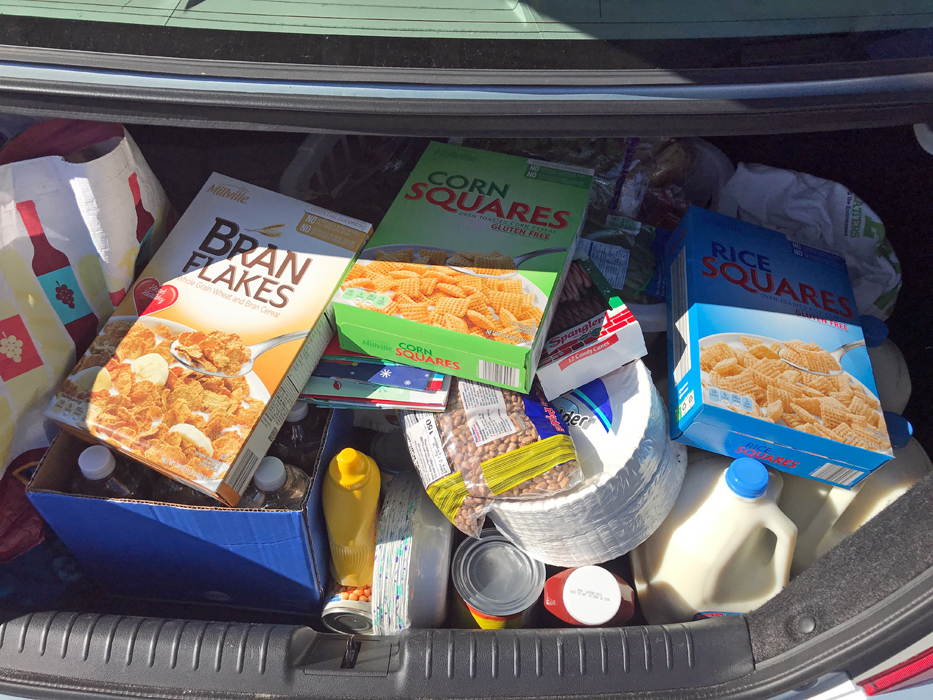 unbagged groceries tossed into trunk of car