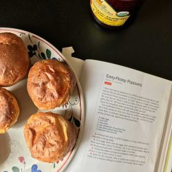 plate of popovers next to cookbook and jar of jam