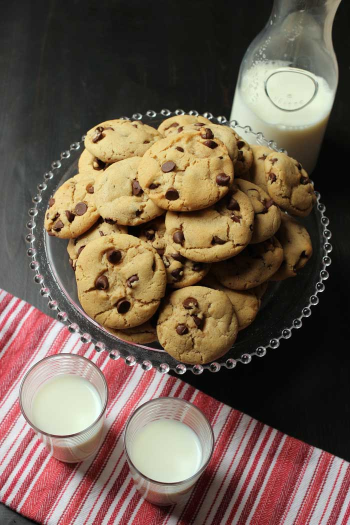 carafe and glasses of milk next to platter of crispy chocolate chip cookies