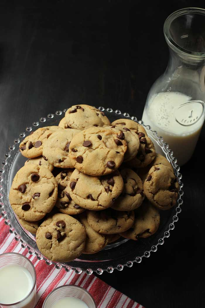 crispy chocolate chip cookies on tray with milk carafe and glasses