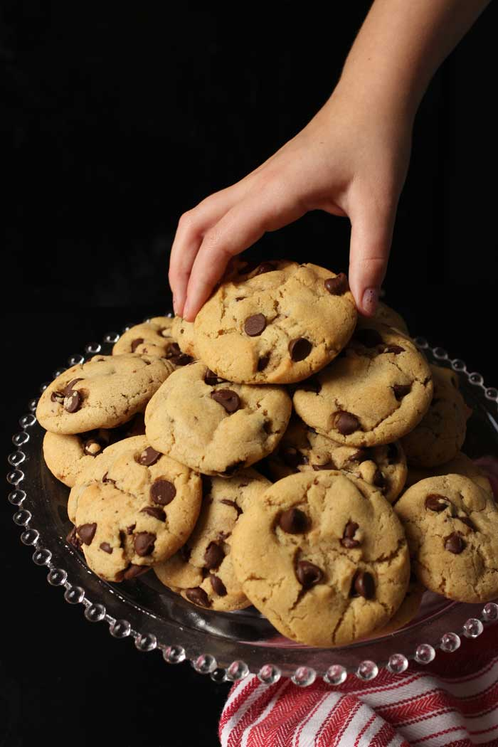 girl's head reaching for chocolate chip cookies on glass stand