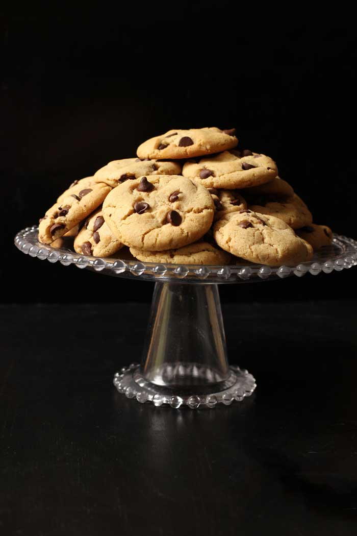 glass cake stand piled with chocolate chip cookies