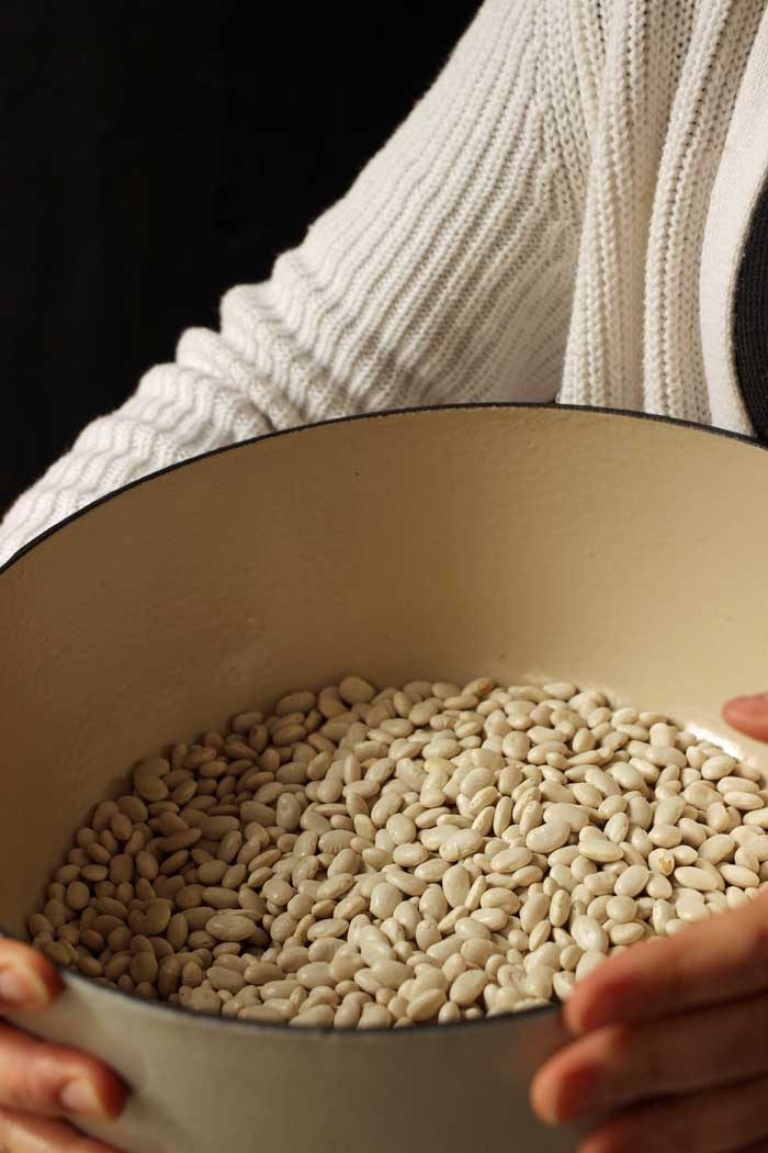 woman holding pot of dried white beans