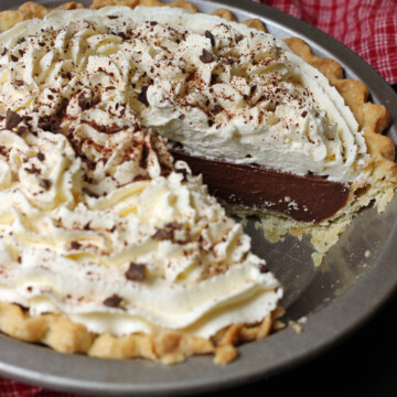 A piece cut out of chocolate cream pie