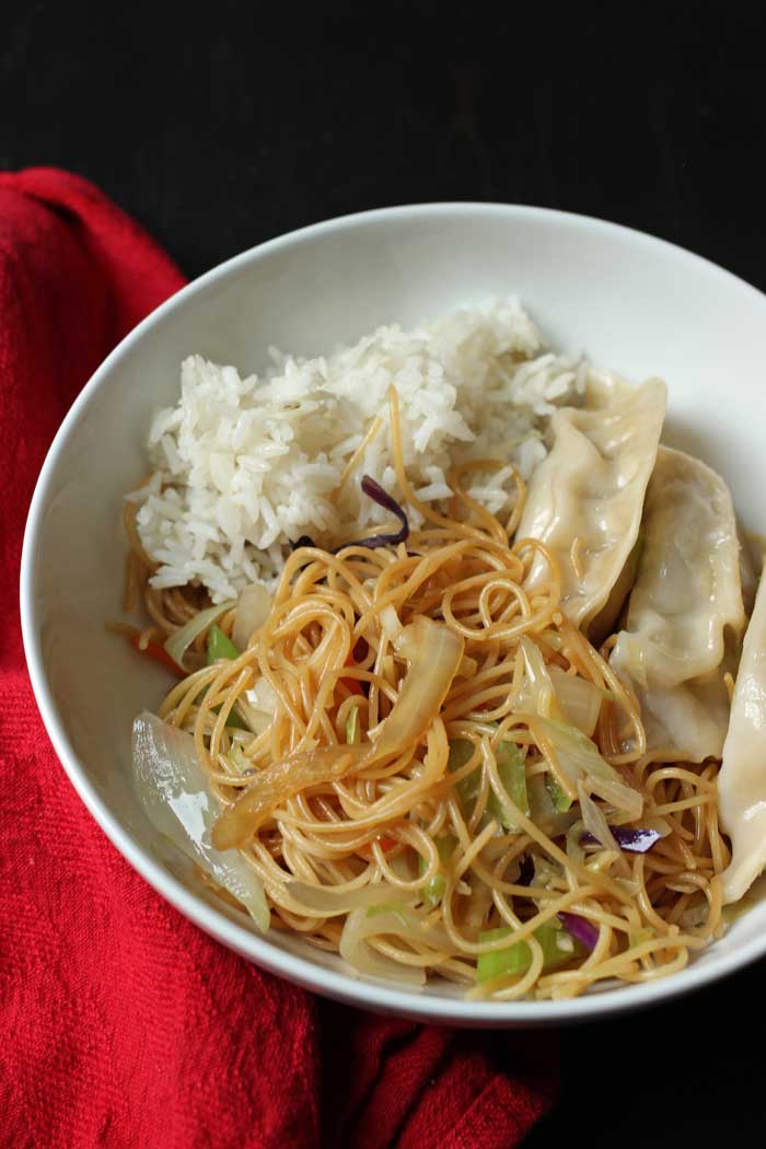 chow mein, rice, and potstickers in a bowl