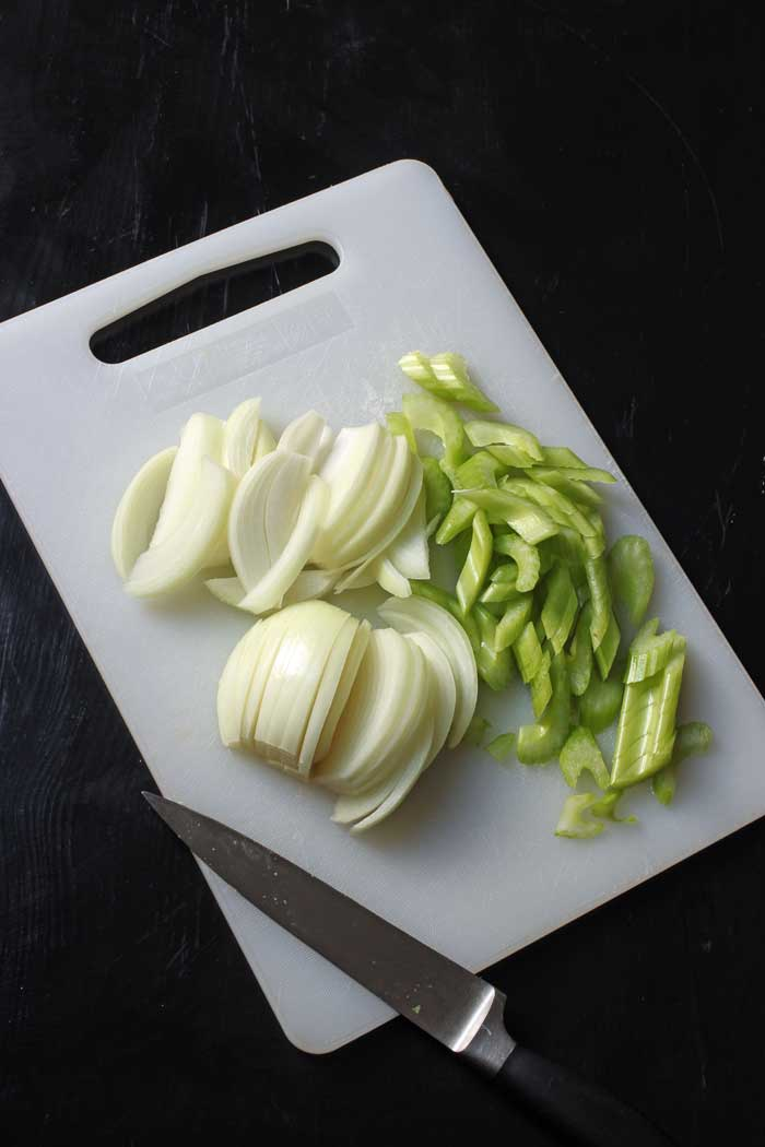 sliced onions and celery on cutting board with knife