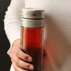 woman holding medicine ball in travel tea mug