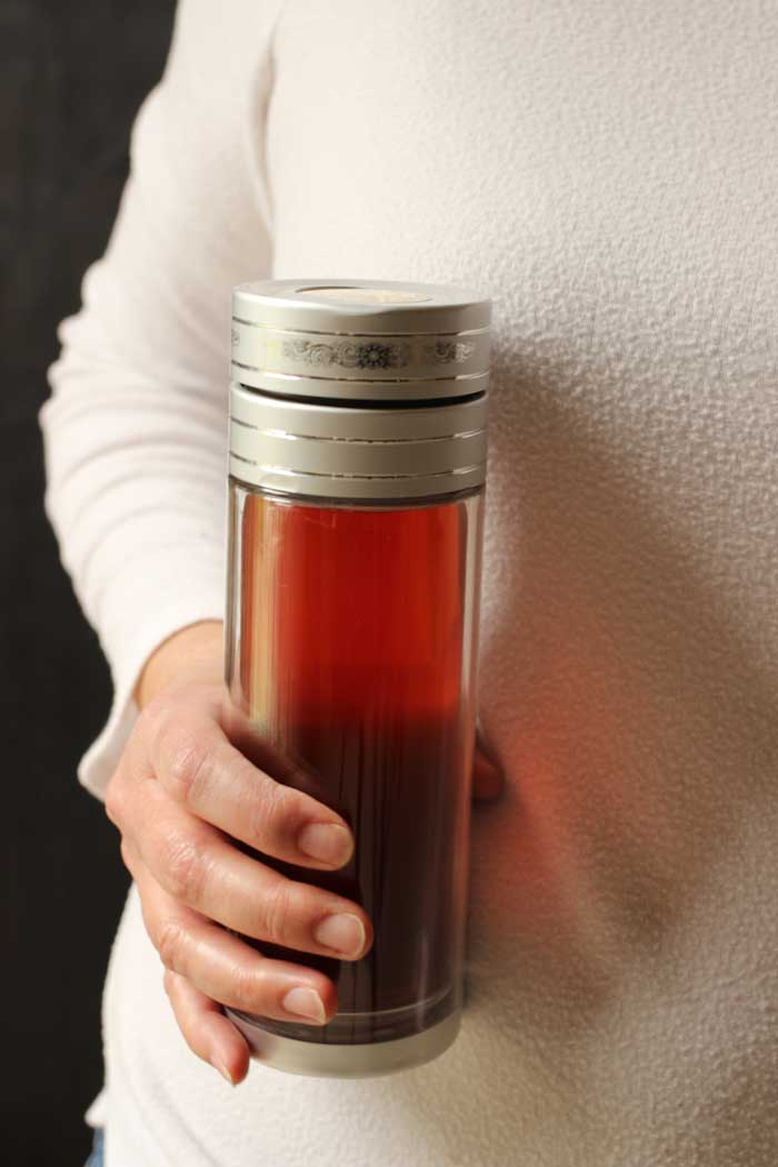 woman holding medicine ball in travel tea mug