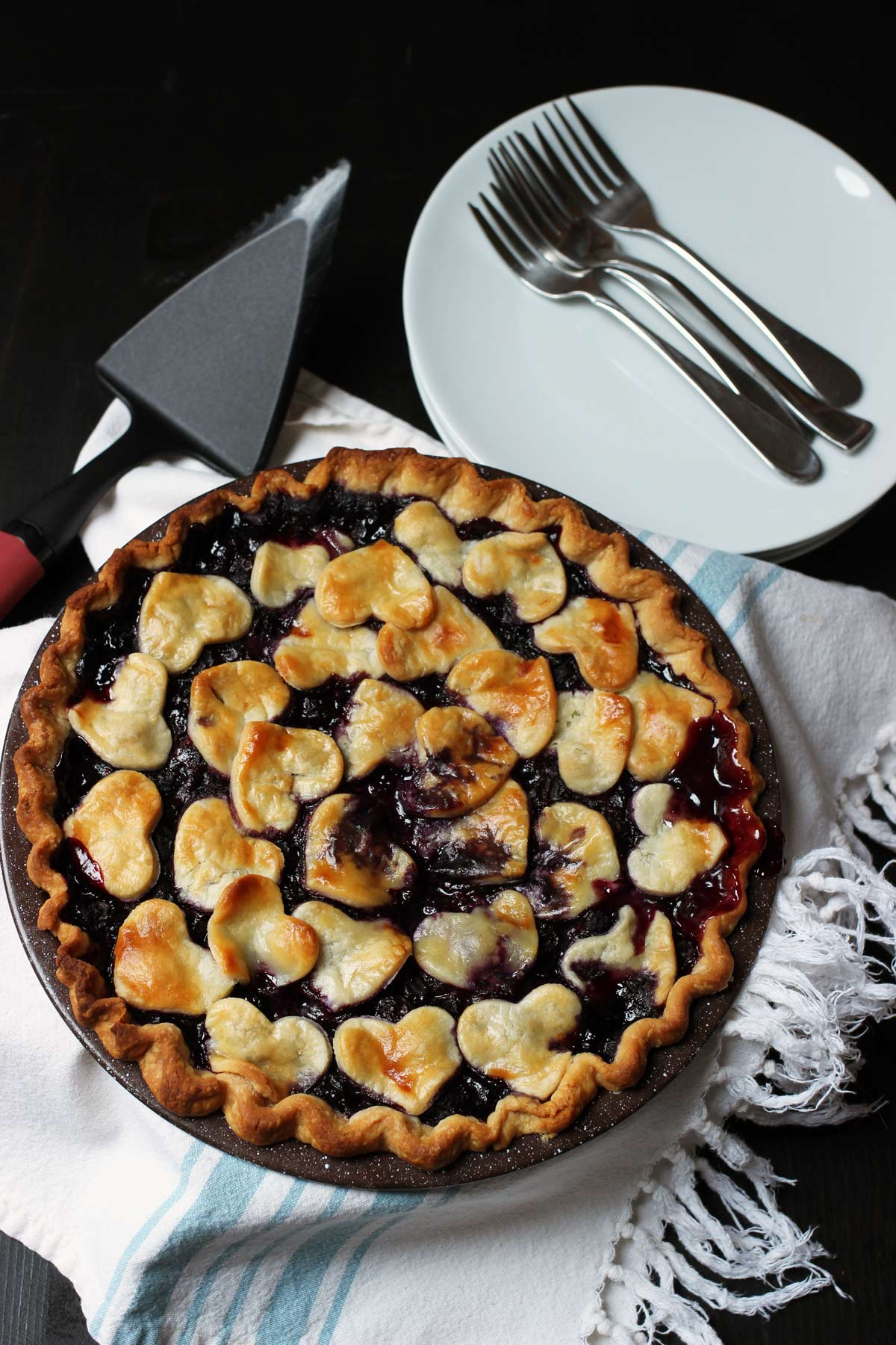 blueberry pie on blue striped cloth with pie server and stack of plates and forks.